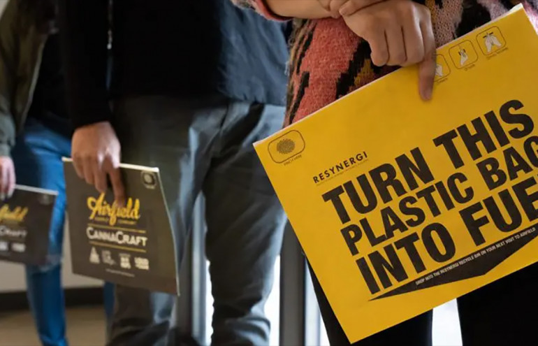 "Photo of sign reading ""Turn this plastic bag into fuel, ""Resynergi Plastic to Fuel program"
